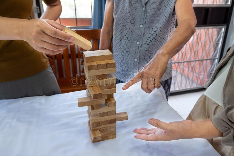 Image of old woman and two girls hand holding blocks wood game to growing up of home business, Risk of management and strategy. Plan stock images