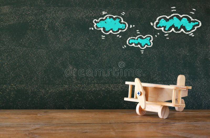 Image of old wooden airplane toy on wooden table in front of set of info graphics over textured chalkboard.  royalty free stock photo