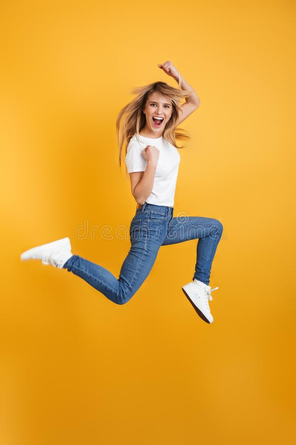 Emotional screaming positive young blonde woman jumping isolated over yellow wall background dressed in white casual t-shirt make. Image of optimistic screaming royalty free stock image