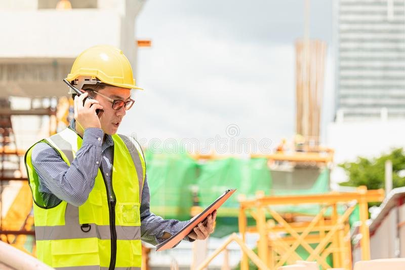 Image outside the industrial construction engineers in yellow protective helmet discuss new project while walkie talkie. And happy smile on the open building stock photo