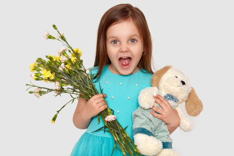 Image of overjoyed blue eyed small child holds her favourite toy and flowers, happy to recieve present on birthday, opens mouth royalty free stock photography