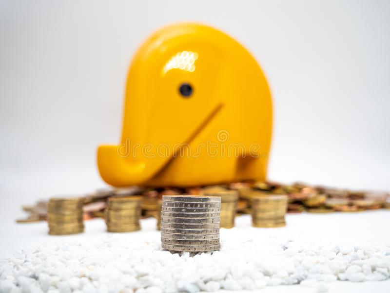 Image of pile of Euro coins with yellow piggy bank in the background close up royalty free stock photo