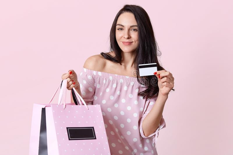 Image of pleased young European woman enjoys shopping on weekend, holds plastic card, shopping bags, spends money on clothes, stock photos
