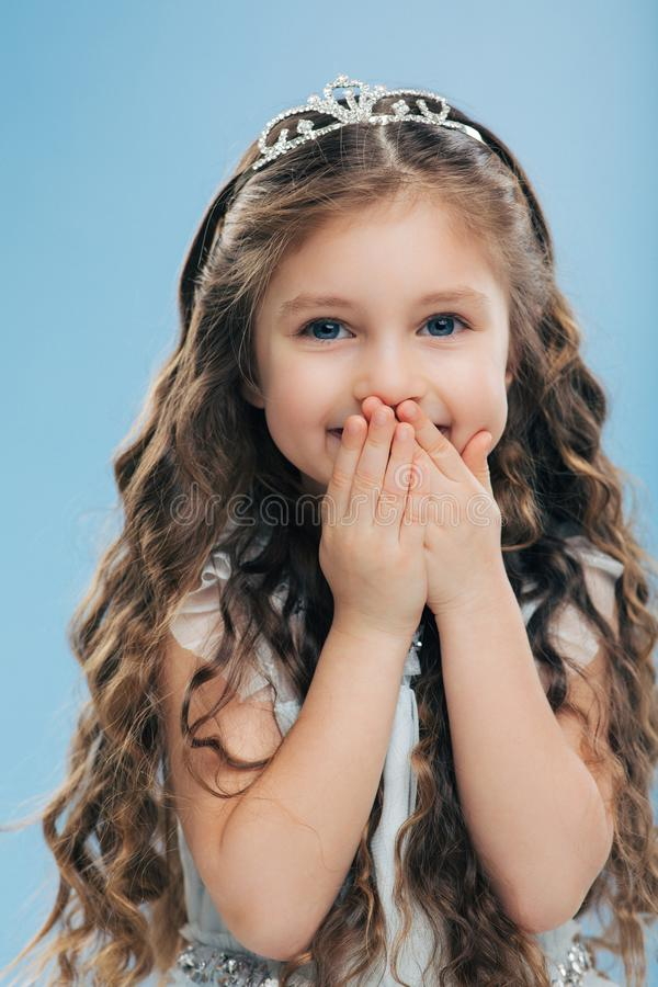 Image of positive beautiful smiling child keeps both hands on mouth, has long thick hair, blue eyes, wears crown, poses against stock photography