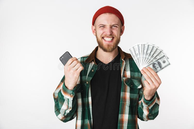 Image of positive guy wearing plaid shirt holding cell phone and dollar money, while standing isolated over white background royalty free stock photo