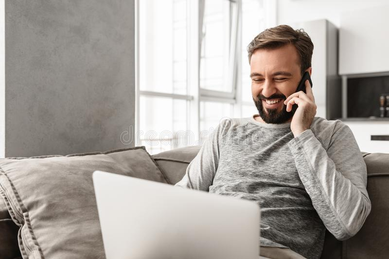 Image of positive man 30s in casual wear sitting on sofa in living room, while using laptop and speaking on cell phone royalty free stock photos