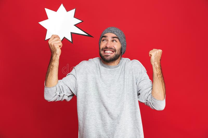 Image of positive man 30s wearing hat holding blank idea poster,  over red background royalty free stock photos