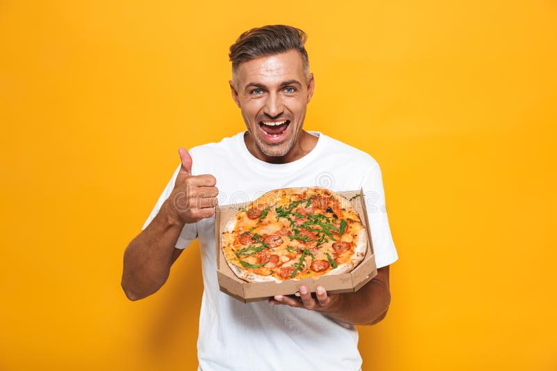 Image of positive man 30s in white t-shirt holding and eating pizza while standing isolated royalty free stock photos