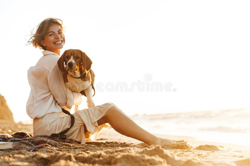 Image of positive woman 20s hugging her dog, while sitting on sand by seaside royalty free stock photography