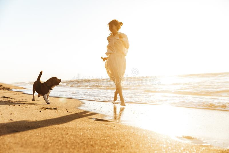 Image of positive woman 20s playing with her dog, while walking by seaside stock image