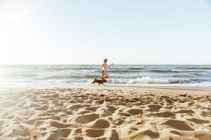 Image of positive woman in straw hat, running with her brown dog along the coast stock photos