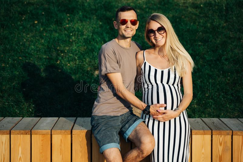 Image of pregnant blonde woman and man standing near wooden fence on summer day stock photo