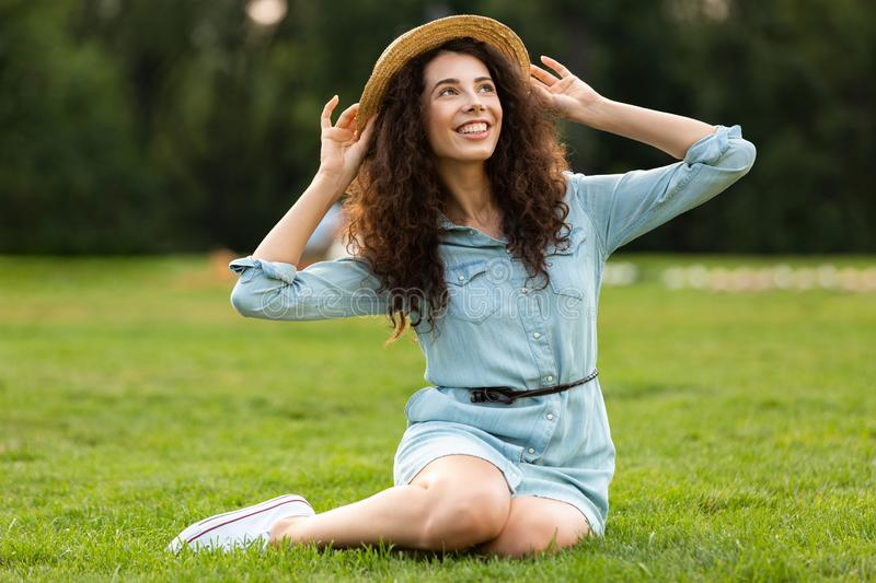 Image of pretty brunette woman wearing straw hat and dress sitting on grass in park stock photo