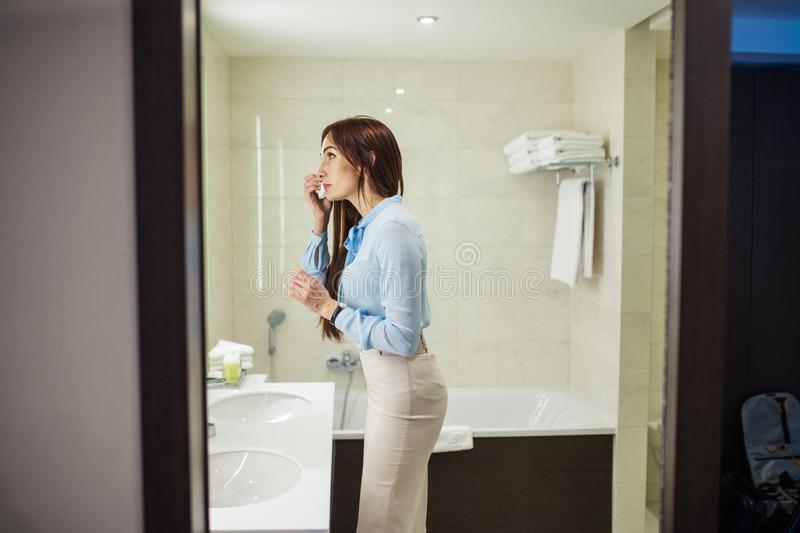Pretty female in formal wear looking at mirror while washing hands in bathroom. Image of pretty female dressed in romantic blue blouse, pencil skirt looking at stock photo