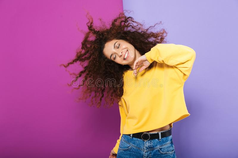 Image of pretty happy curly woman swearing casual clothes smiling and dancing stock images