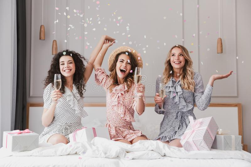 Image of pretty happy women 20s wearing dresses celebrating bridal shower in posh apartment, with champagne and confetti. Image of pretty happy women 20s wearing stock photography