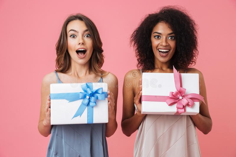 Pretty shocked young two women holding gifts stock image