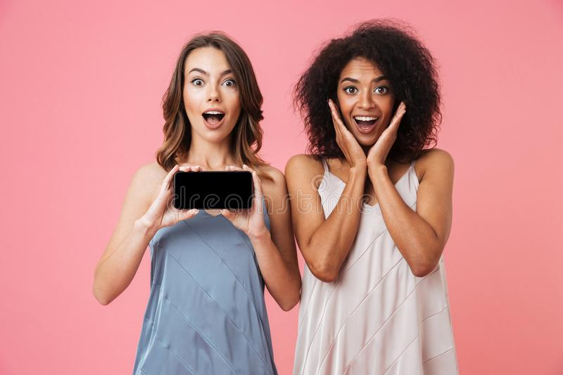 Pretty shocked young two women showing display of mobile phone. stock photography