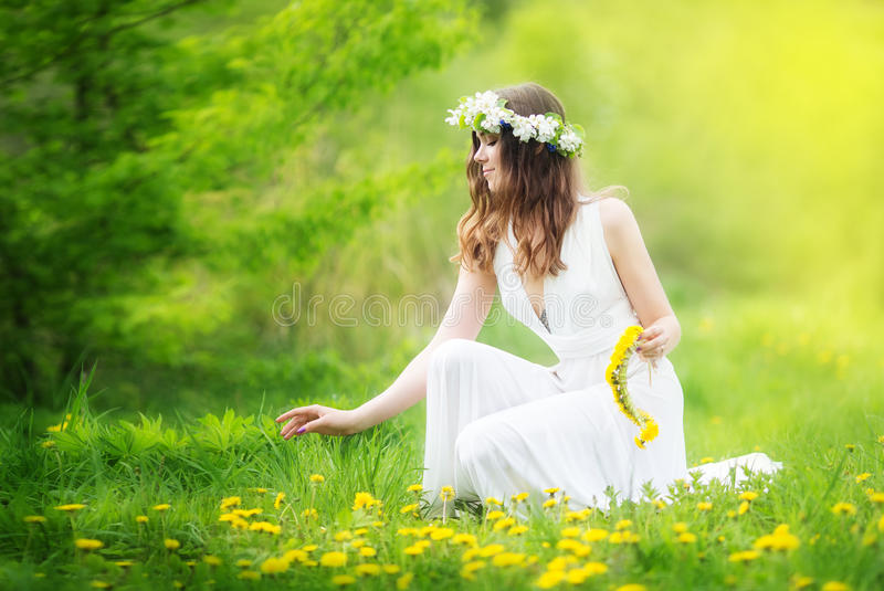 Image of pretty woman in a white dress weaves garland from dandelions in the field, happy cheerful girl resting on dandelions me stock photography