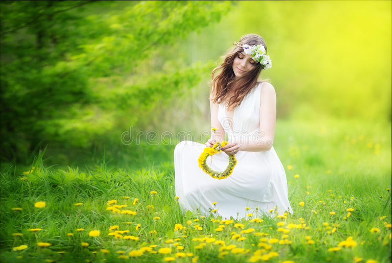 Image of pretty woman in a white dress weaves garland from dandelions in the field, happy cheerful girl resting on dandelions me royalty free stock images