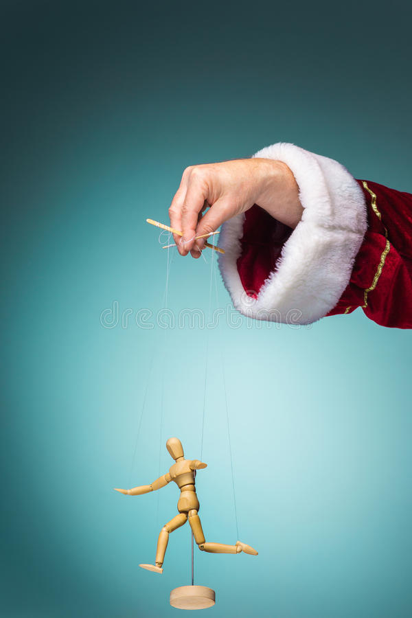 Image puppet in the hands of Santa. Image puppet in the hands of the Santa as puppeteer on blue background stock images