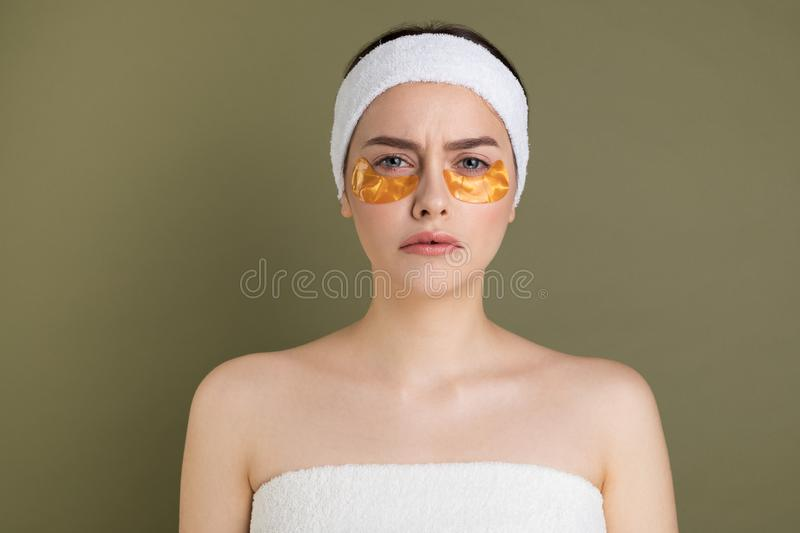 Image of pure beautiful gentel girl with naked shoulders. Looking at camera, take care of her skin with under eyes patches stock photography
