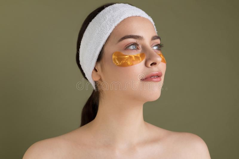 Image of pure beautiful gentel girl with naked shoulders. Looking away, take care of her skin with under eyes patches royalty free stock photography