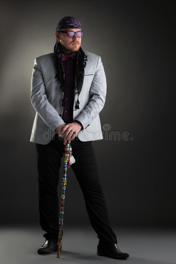Image of racy man posing with cane in studio. On gray background royalty free stock image