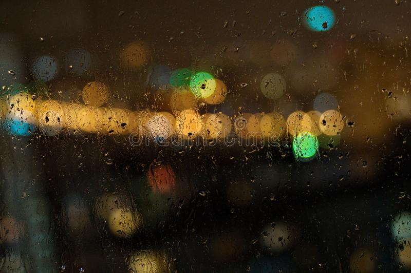 Image of raindrops on window at night in the city royalty free stock image