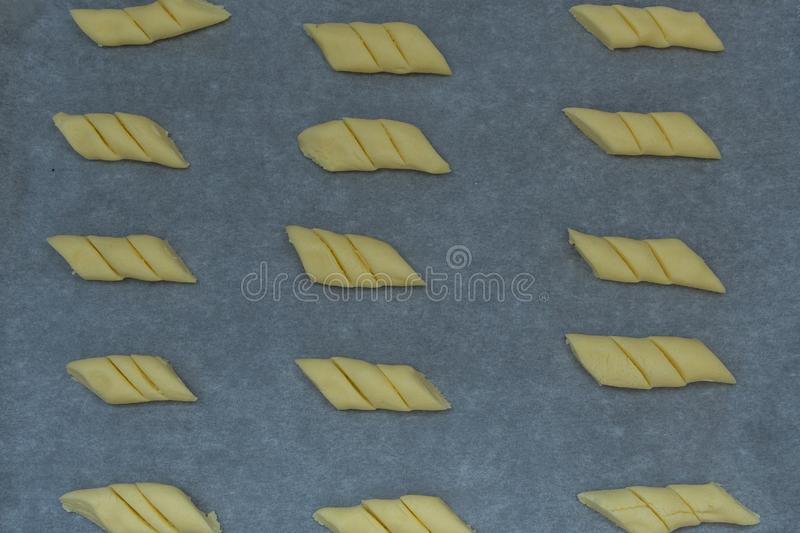 Image of raw cornstarch cookies on waxed paper in a baking tray ready to be baked royalty free stock photography