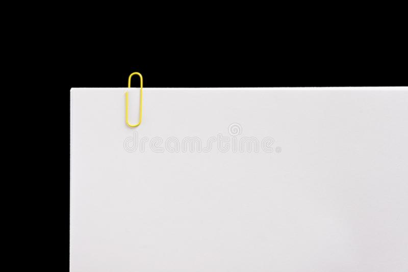 White sheet with clips on black background. royalty free stock photo
