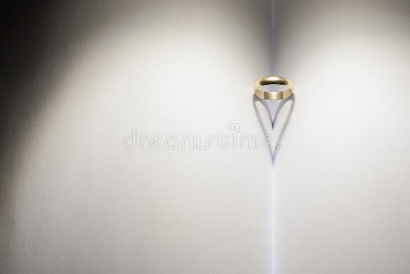 Ring forming a heart of shadow on a book. royalty free stock photos