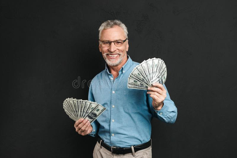 Image of rich good-looking adult man 60s with gray hair holding royalty free stock photography
