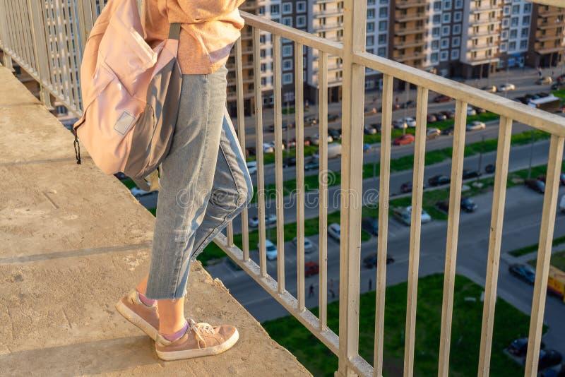 Image rognée d'une fille en jeans et baskets avec sac à dos debout sur un balcon contre un immeuble résidentiel haut de plusieurs image libre de droits
