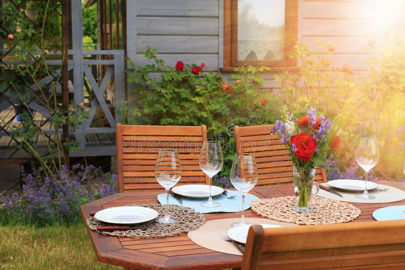 Image of a romantic table setting, for a wedding or garden party. Romantic table setting, for a wedding or garden party. Wooden table for dinner, served with stock photography
