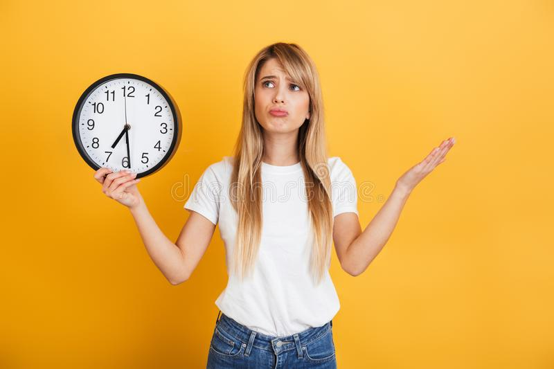 Thinking young blonde woman posing  over yellow wall background dressed in white casual t-shirt holding clock. Image of a sad thinking young blonde woman posing royalty free stock images