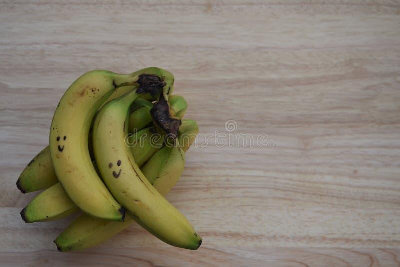 Image saine de photographie de nourriture avec le fruit frais des bananes avec tiré sur le sourire heureux sur le fond en bois ru photos libres de droits