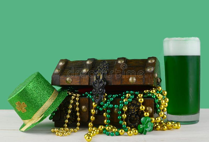 Image for Saint Patrick`s Day on March 17th. Treasure chest to symbolize luck and wealth with a glass of green beer. stock photography