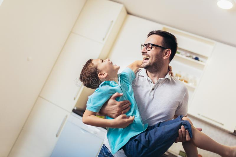 Satisfied smiling man piggybacking his son while having fun in modern studio apartment royalty free stock images