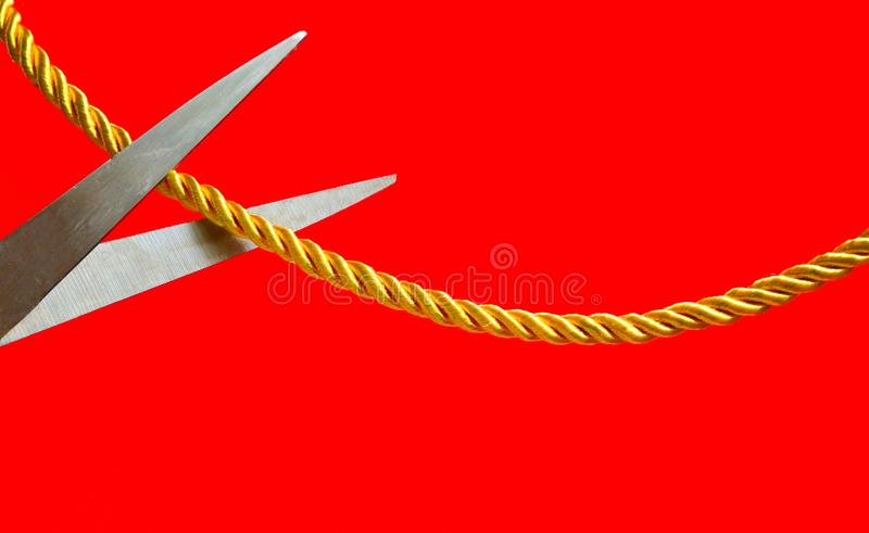 Cut off relationship. Image of scissors cutting a cord which tied between two sides on red background, cutting relationship concept stock photography