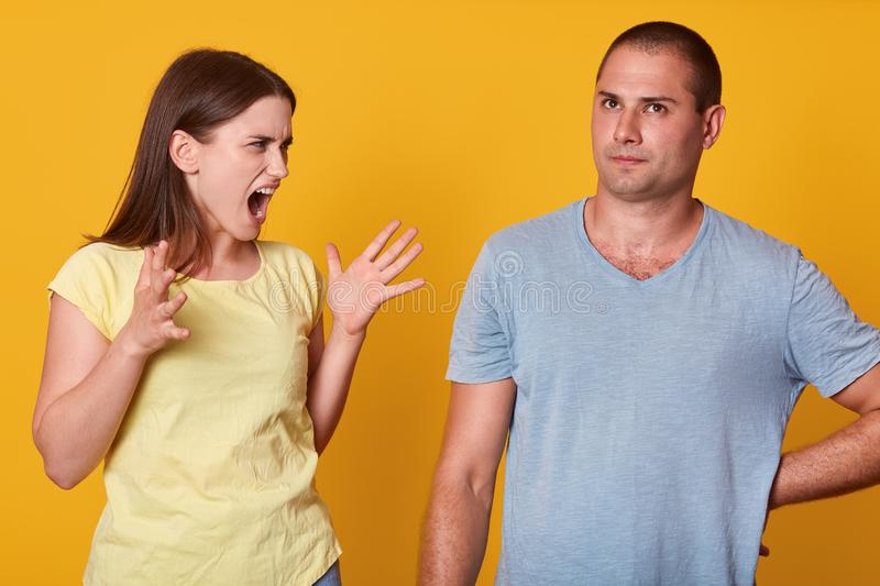 Image of screaming angry woman raising her hands, having quarrel with her husband, looking at him with anger. Calm slender man stock photo