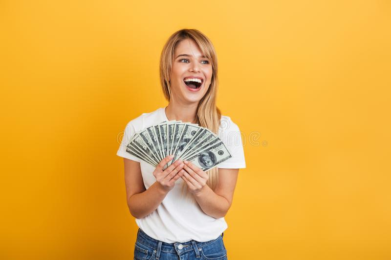 Screaming emotional young blonde woman posing isolated over yellow wall background dressed in white casual t-shirt holding money. Image of a screaming emotional stock photo