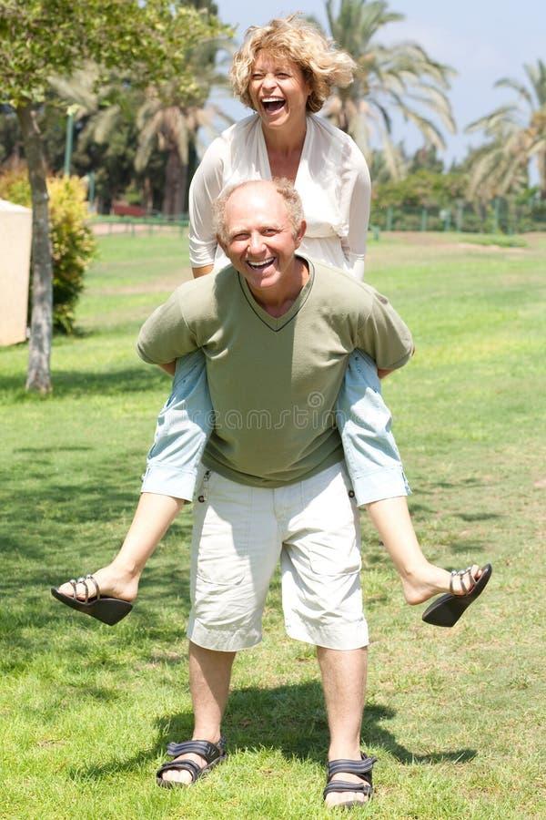 Image of Senior man giving woman piggyback ride royalty free stock photography