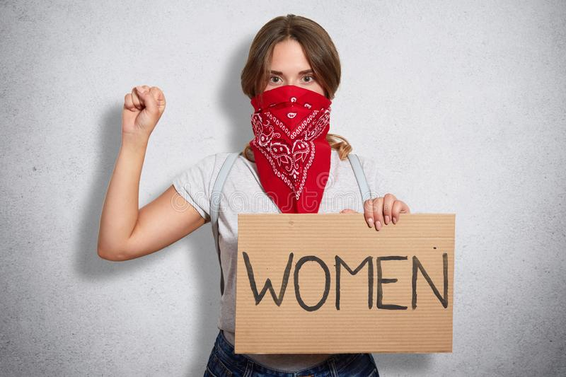 Image of serious bossy militant young feminist raising arm, showing fist, holding sign in one hand, having inscription women on. Image of serious bossy militant royalty free stock photos