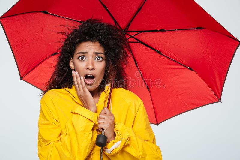 Image of shocked african woman in raincoat hiding under umbrella stock image