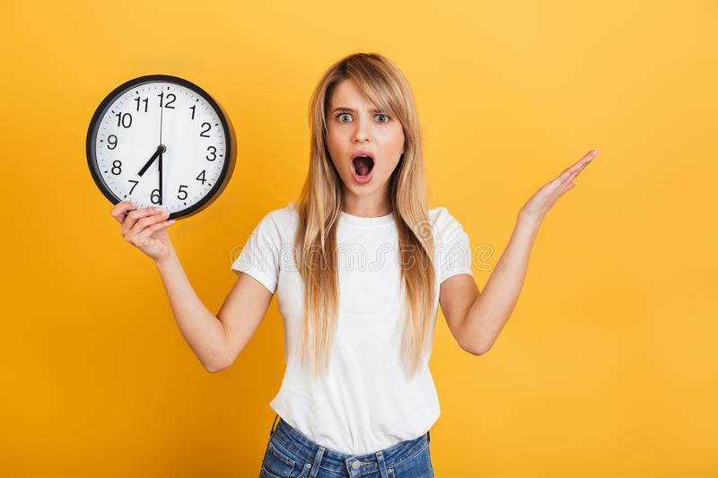 Shocked displeased young blonde woman posing isolated over yellow wall background dressed in white casual t-shirt holding clock. Image of a shocked displeased stock images