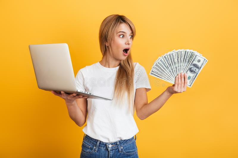 Shocked emotional young blonde woman posing  over yellow wall background dressed in white casual t-shirt using laptop royalty free stock photography