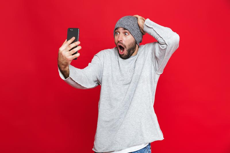 Image of shocked man 30s grabbing head and holding smartphone while standing,  over red background. Image of shocked man 30s grabbing head and holding smartphone royalty free stock photo