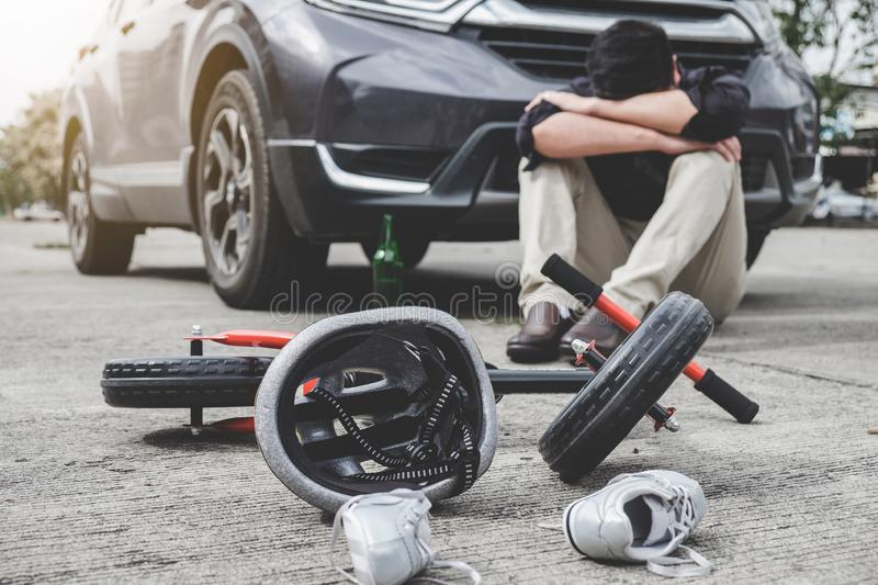 Image of shocked and scared driver after accident involved Kid`s bike and helmet lying on the road on pedestrian crossing after stock image