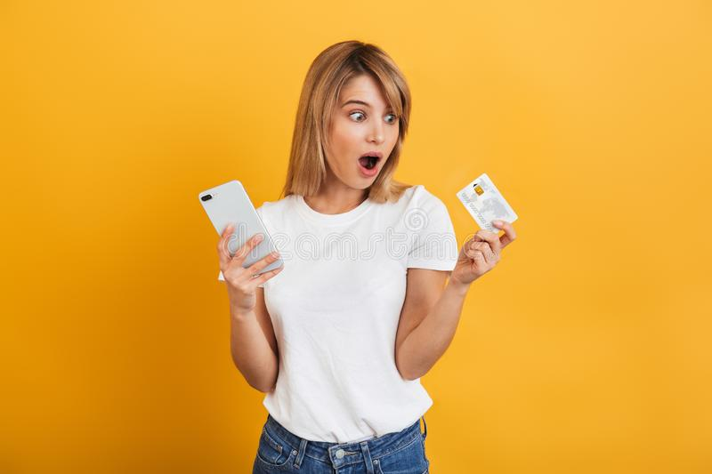 Shocked surprised young blonde woman posing isolated over yellow wall background dressed in white casual t-shirt using mobile royalty free stock photography